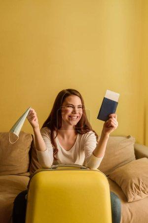 glückliche junge Frau mit medizinischer Maske, Reisepass und Flugticket in der Nähe des Gepäcks, Ende der Quarantäne