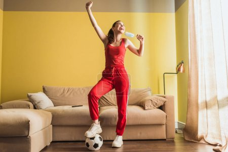 Photo for Happy sportswoman with hand above head touching medical mask and standing near football in living room, end of quarantine concept - Royalty Free Image