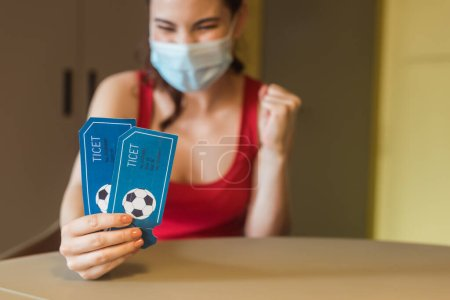 selective focus of happy woman in medical mask holding sport match tickets