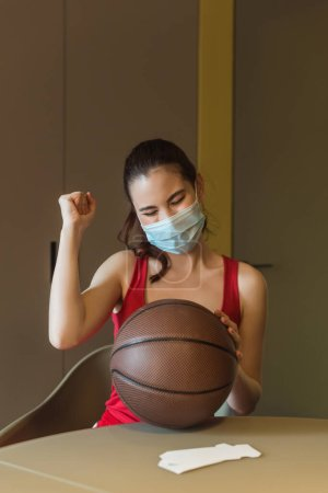 sportive woman in medical mask and closed eyes cheering near basketball