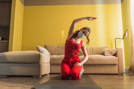 Photo for Young woman in medical mask and hand on hip exercising on fitness mat - Royalty Free Image