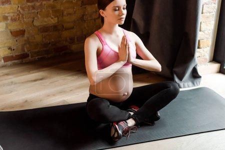 Photo pour Femme enceinte avec les mains priantes assis dans la pose de lotus sur tapis de fitness - image libre de droit
