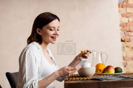 Photo pour Happy and pregnant woman using smartphone near tasty breakfast - image libre de droit