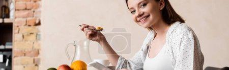 Photo pour Image horizontale de la femme enceinte tenant cuillère avec des flocons de maïs et smartphone - image libre de droit
