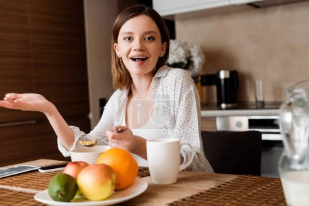 Photo pour Foyer sélectif de femme excitée tenant cuillère avec des flocons de maïs près des fruits - image libre de droit