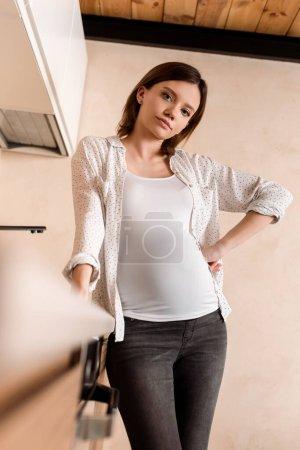 Selektiver Fokus einer Schwangeren, die mit der Hand auf der Hüfte steht