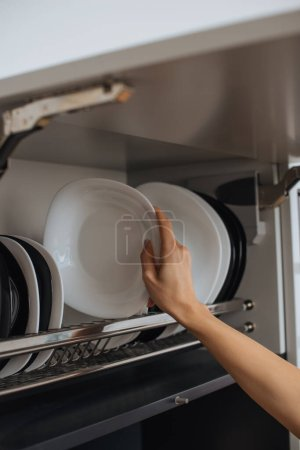 cropped view of housewife placing clean plate on rack in kitchen