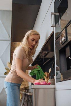 Photo pour Jeune femme au foyer tenant des gants en caoutchouc tout en essuyant la surface de la cuisine avec chiffon - image libre de droit