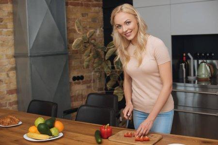 Foto de Mujer feliz mirando a la cámara mientras cortan verduras frescas en el tablero de picar. - Imagen libre de derechos