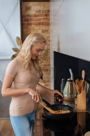 young blonde woman pouring red wine into wok while preparing thai noodles