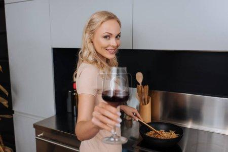 Photo pour Foyer sélectif de la jeune femme tenant un verre de vin rouge et souriant à la caméra tout en préparant des nouilles thai - image libre de droit