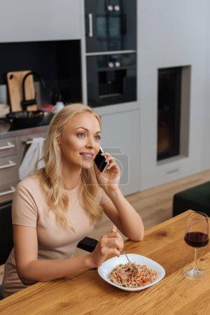 Photo pour Femme souriante parlant sur smartphone tout en étant assis près de la plaque avec des nouilles thai et un verre de vin rouge - image libre de droit
