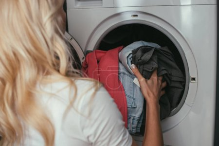 Photo for Back view of housewife putting laundry into washing machine - Royalty Free Image