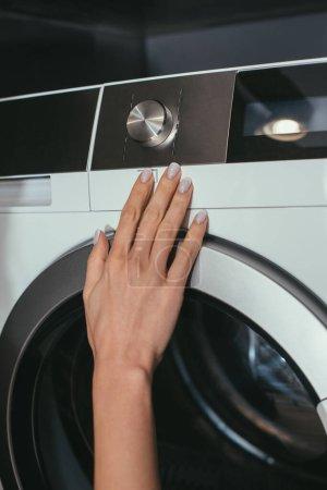 Photo pour Vue recadrée de la femme au foyer touchant panneau de commande de la machine à laver - image libre de droit