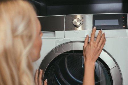Photo pour Vue arrière de la femme au foyer touchant panneau de commande de la machine à laver - image libre de droit