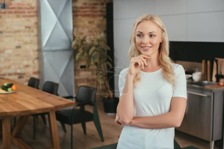 happy blonde woman looking away and holding hand near chin while standing at home