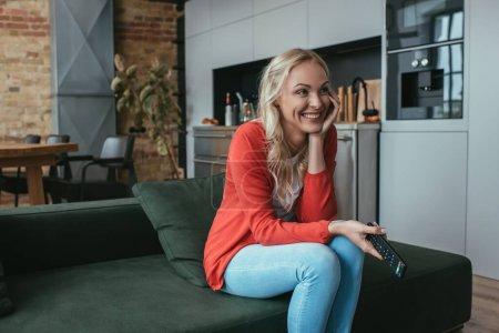 Photo pour Femme gaie riant tout en regardant la télévision à la maison - image libre de droit