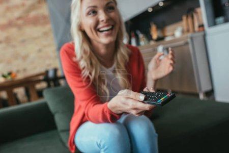 Photo pour Foyer sélectif de femme gaie riant tout en regardant la télévision à la maison - image libre de droit