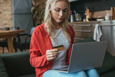 jeune femme attentive tenant la carte de crédit tout en utilisant un ordinateur portable