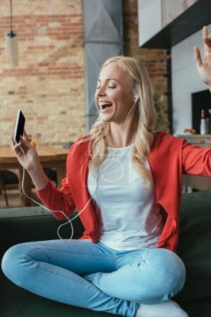 Photo pour Femme heureuse dans les écouteurs chantant avec les yeux fermés et la main levée tout en tenant smartphone - image libre de droit
