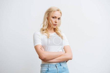 Photo pour Offensé femme debout avec les bras croisés tout en regardant la caméra isolée sur blanc - image libre de droit