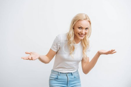 cheerful blonde woman standing with open arms while smiling at camera isolated on white