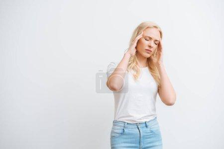 Photo pour Femme épuisée avec les yeux fermés touchant la tête tout en souffrant de migraine isolé sur blanc - image libre de droit