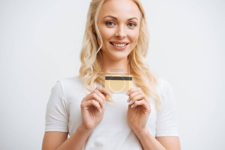 Photo for Smiling blonde woman showing credit card and looking at camera isolated on white - Royalty Free Image