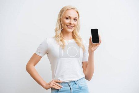 Photo pour Femme heureuse tenant la main sur la hanche tout en montrant smartphone avec écran vide et souriant à la caméra isolée sur blanc - image libre de droit