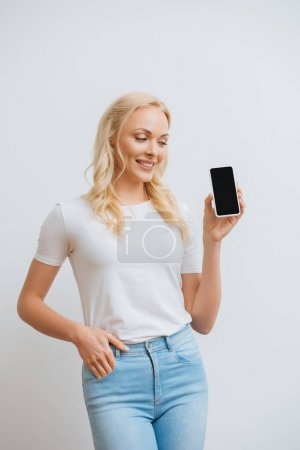Photo for Smiling woman holding hand in pocket while looking at smartphone with blank screen isolated on white - Royalty Free Image