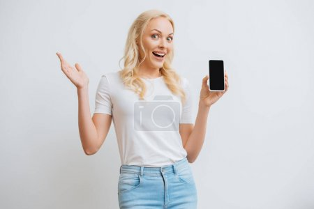 excited woman showing smartphone with blank screen while looking at camera isolated on white