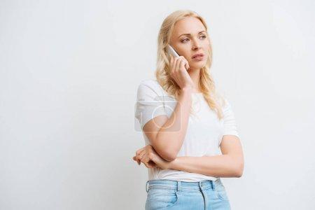 Photo pour Bouleversé femme blonde parler sur smartphone et regarder loin isolé sur blanc - image libre de droit