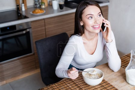 happy girl talking on smartphone and laughing while holding spoon with delicious corn flakes and milk
