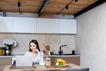 attraktive Freelancer mit Laptop in der Nähe leckeres Frühstück zu Hause