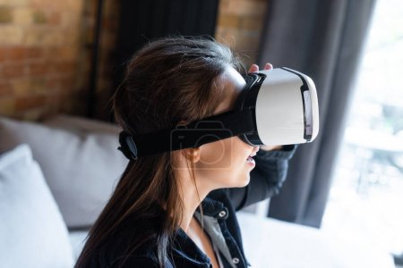 Photo for Excited woman in virtual reality headset at home - Royalty Free Image