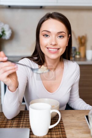 selective focus of happy girl holding spoon with corn flakes