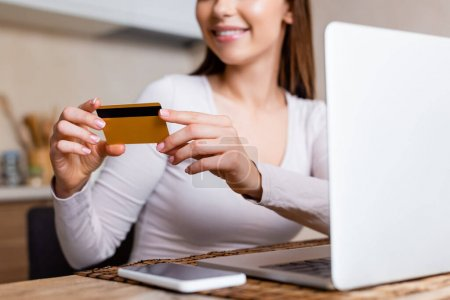 cropped view of happy girl holding credit card near laptop and smartphone on table