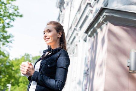 Photo pour Jeune femme joyeuse veste en denim tenant une tasse de café dehors - image libre de droit