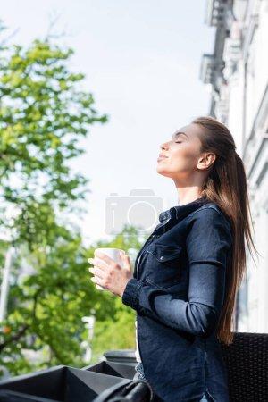 Photo pour Vue latérale de la jeune femme joyeuse avec les yeux fermés tenant tasse de café à l'extérieur - image libre de droit