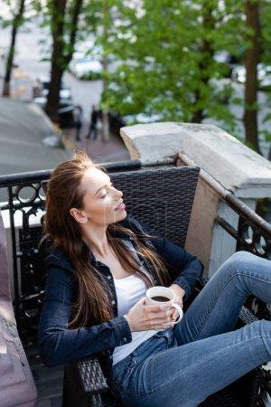 Photo pour Gaie fille en jeans denim et veste assis sur la chaise et tenant une tasse de café sur le balcon - image libre de droit