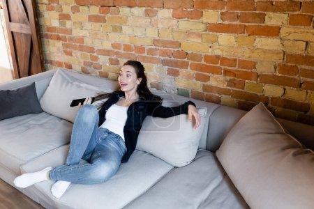 Photo pour Excité femme assis sur canapé et regarder le film - image libre de droit