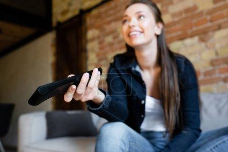 selektiver Fokus der jungen und glücklichen Frau, die Fernbedienung hält, während sie einen Film anschaut