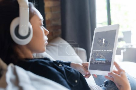 KYIV, UKRAINE - APRIL 29, 2020: selective focus of girl in wireless headphones listening music and using digital tablet with tumblr app