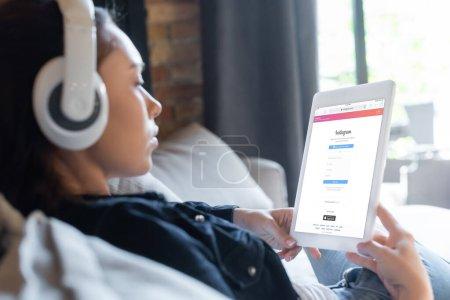 Photo pour KYIV, UKRAINE - 29 AVRIL 2020 : mise au point sélective de la fille dans les écouteurs sans fil écouter de la musique et utiliser une tablette numérique avec l'application instagram - image libre de droit