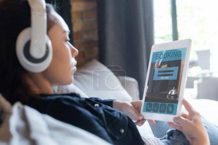 Photo pour Foyer sélectif de la fille dans les écouteurs sans fil écouter de la musique et en utilisant une tablette numérique avec application de réservation - image libre de droit