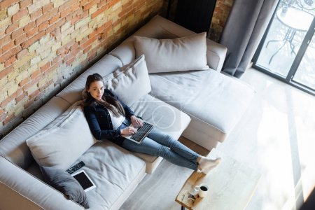 overhead view of attractive freelancer using laptop near digital tablet with blank screen on sofa