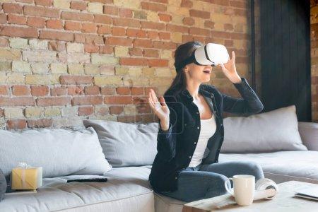 Photo pour Femme excitée toucher casque de réalité virtuelle tout en étant assis sur le canapé - image libre de droit