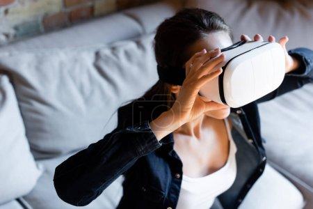 Photo pour Foyer sélectif de la jeune femme touchant casque de réalité virtuelle - image libre de droit