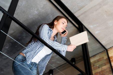 Photo pour Vue à faible angle de la jeune femme parlant sur smartphone tout en tenant le livre - image libre de droit