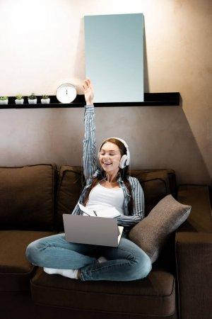 Photo pour Femme heureuse dans les écouteurs sans fil avec la main au-dessus de la tête près de l'ordinateur portable et ordinateur portable dans le salon, concept d'étude en ligne - image libre de droit